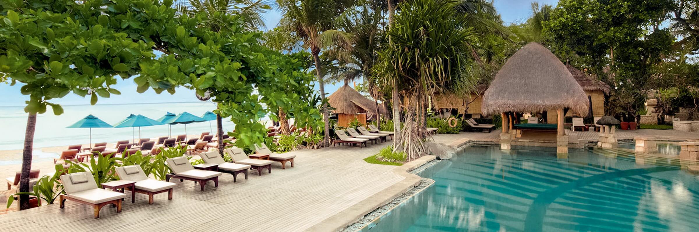 Sonnenliegen am Pool unweit des Strandes des Novotel Bali Benoa Resorts