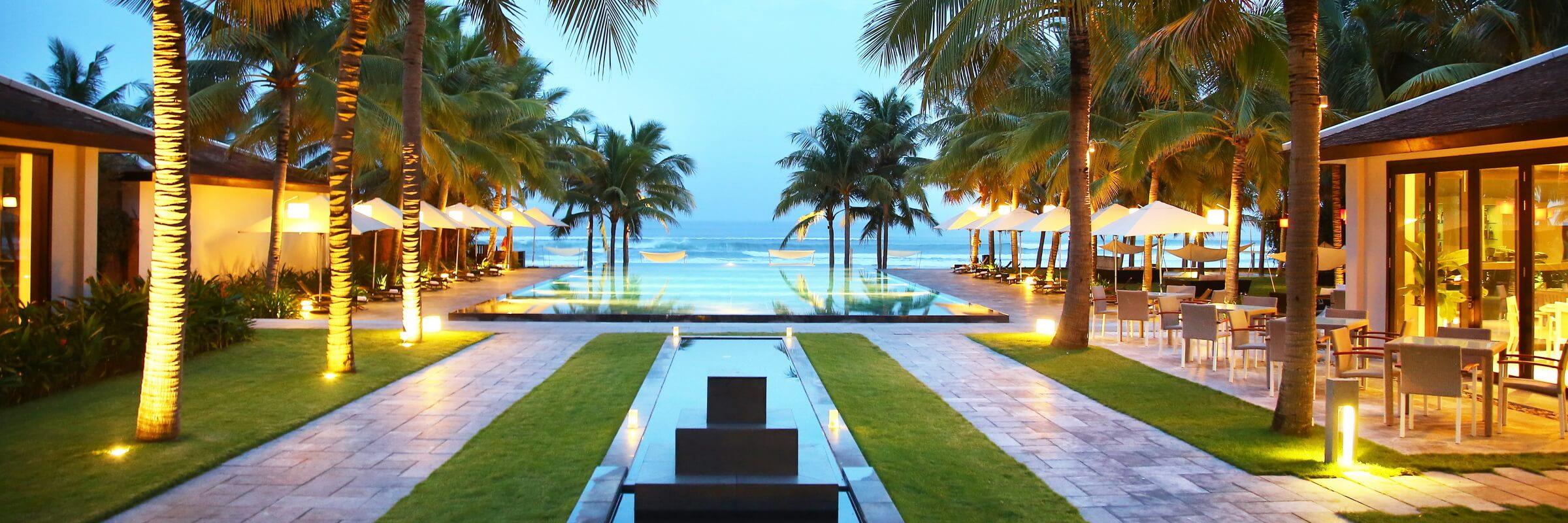 Der einladende Pool mit Sonnenterasse mit direktem Panorama Blick auf das Meer im Fusion Maia Danang Resort
